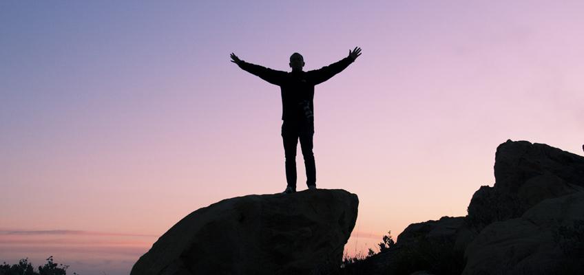 Mann breitet Arme über Klippe aus