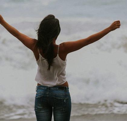Frau steht mit ausgebreiteten Armen vor Meer