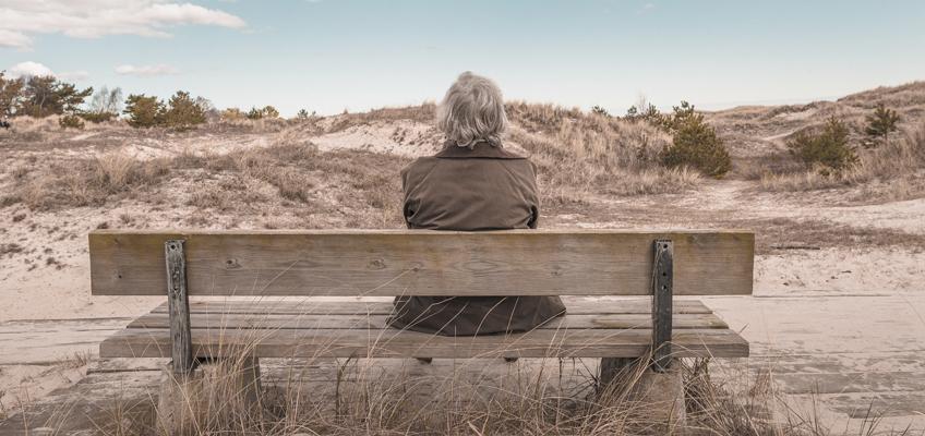 Alter Mann sitzt auf Bank