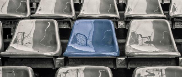 Blauer Tribünen-Stuhl zwischen grauen Stühlen