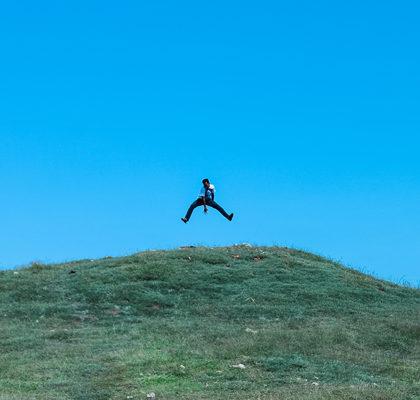 Mann macht Luftsprung auf Berg