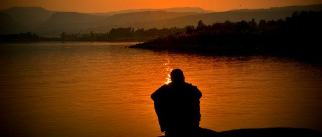 Mann sitzt bei Sonnenuntergang am See