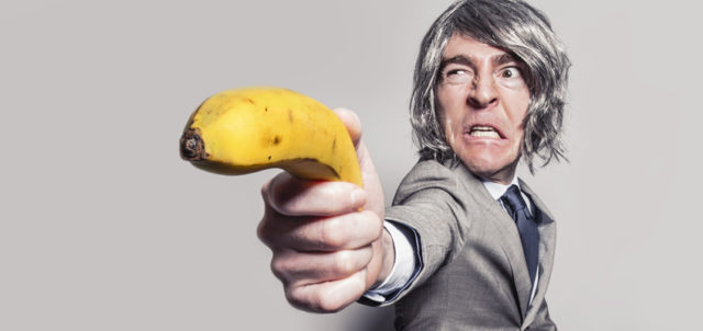 Mann zielt mit Banane als Waffe