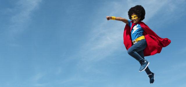 Kind im Superman-Kostüm macht Luftsprung