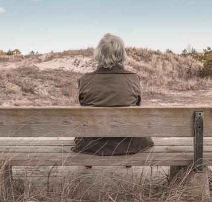 Mann sitzt auf Bank
