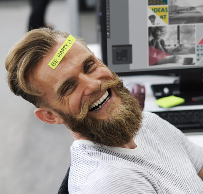 Mann mit Be Happy-Post-it auf Stirn