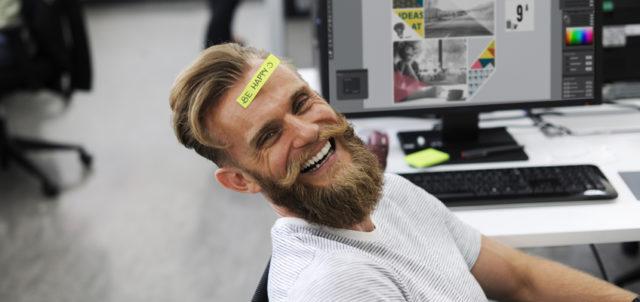 Mann mit Be Happy-Post-it auf Stirn