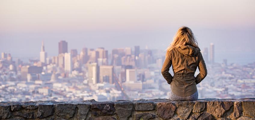 Frau sitzt auf Mauer und schaut auf Skyline