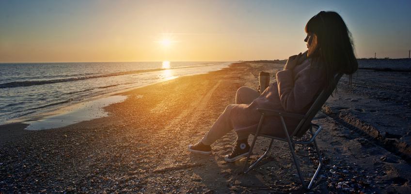 Frau mit Stuhl am Strand