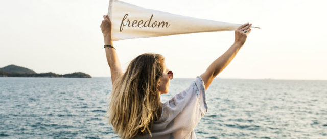 Frau hält Wimpel mit Schriftzug Freedom in die Luft