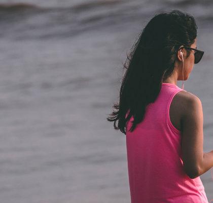 Frau mit Handy am Wasser