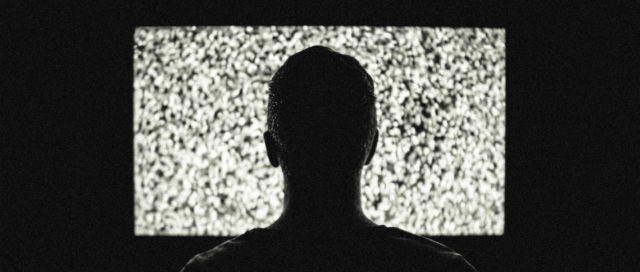 Mann sitzt vor Fernseher