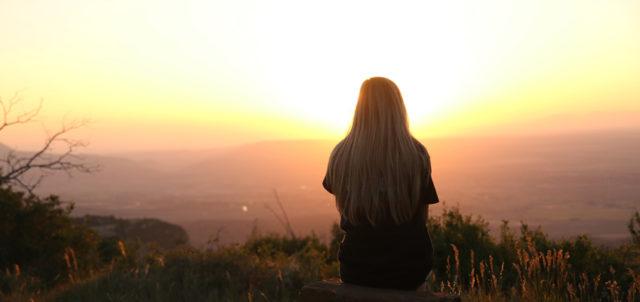 Frau sitzt auf Berg und schaut in Sonnenuntergang