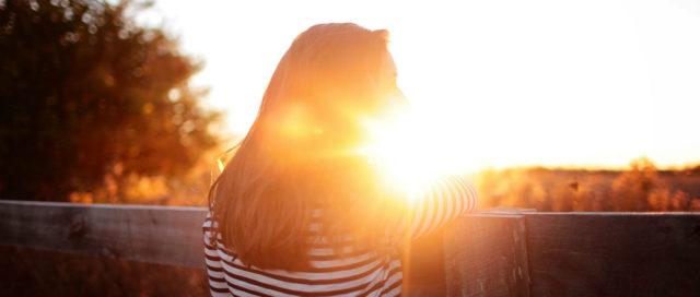 Frau am Zaun schaut in Sonnenuntergang