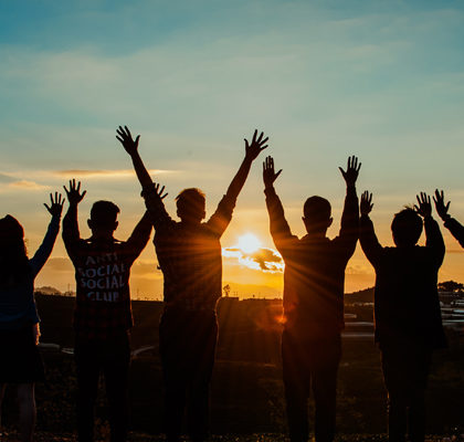 7 Personen heben Arme vor Sonnenaufgang in die Höhe