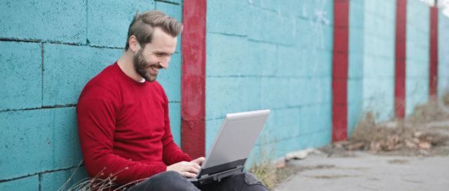 Mann sitzt mit Laptop auf Boden