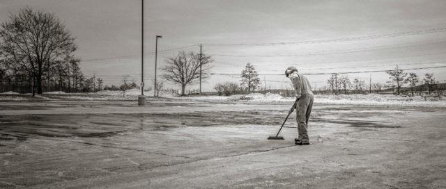 Mann fegt Parkplatz