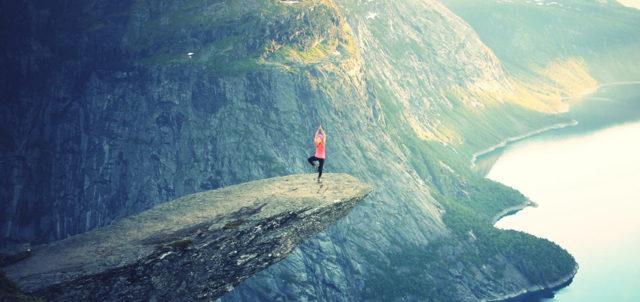 Frau steht mit Yoga-Pose an Klippe
