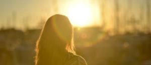 Frau schaut in Sonnenuntergang