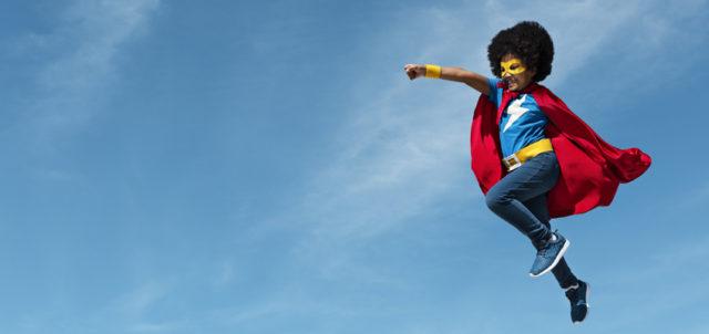 Kind in Superman-Kostüm springt in die Luft