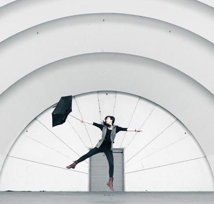 Frau springt mit Regenschirm in die Luft