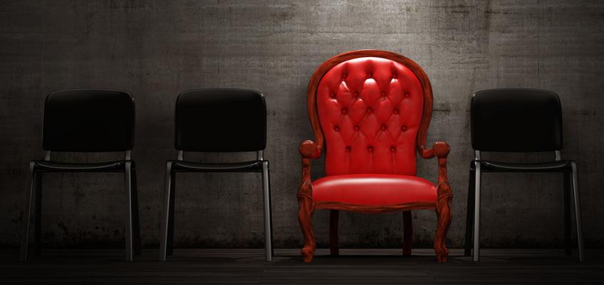 Roter Stuhl zwischen schwarzen Stühlen