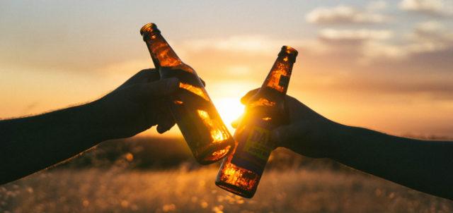 2 prosten sich mit Bierflaschen zu