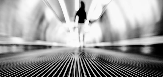 Frau auf Rolltreppe