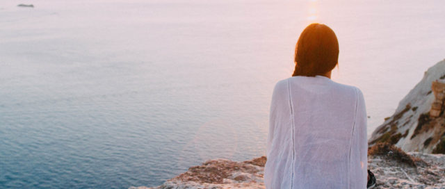 Frau schaut von Klippe aufs Meer