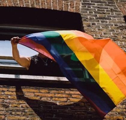 Eine Regenbogenfahne hängt aus einem Fensger