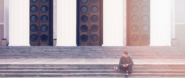 Mann sitzt auf Treppe