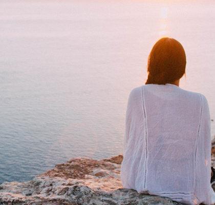 Frau sitzt an Klippe am Meer