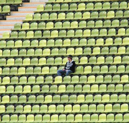 Mann sieht einsam auf Tribüne