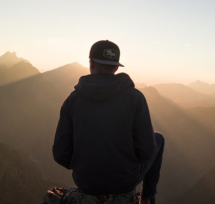 Junge sitzt auf Berggipfel
