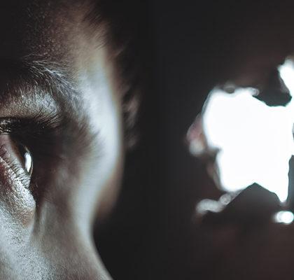 Person schaut durch Loch in Wand