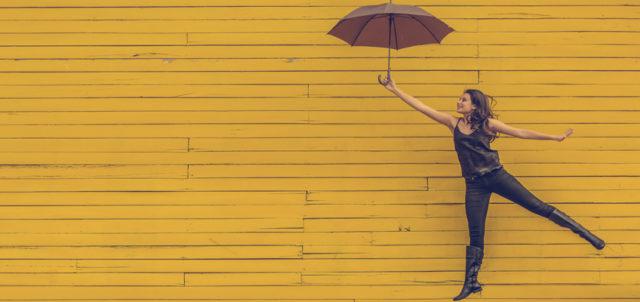 Frau springt mit geöffneten Regenschirm vor einer gelben Wand hoch