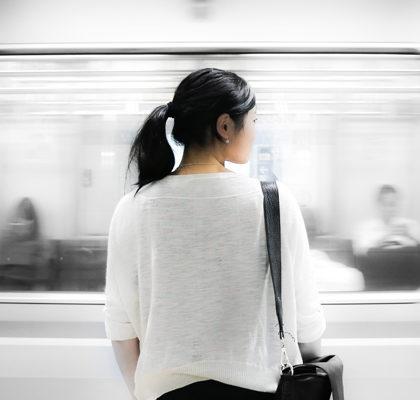 Frau steht vor vorbeifahrender U-Bahn