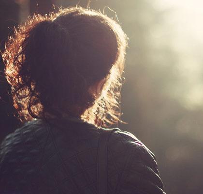 Frau schaut in den Sonnenuntergang