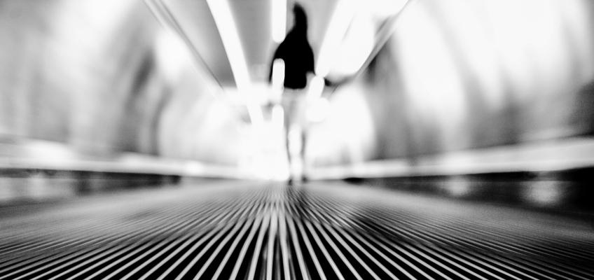 Frau auf Rolletreppe