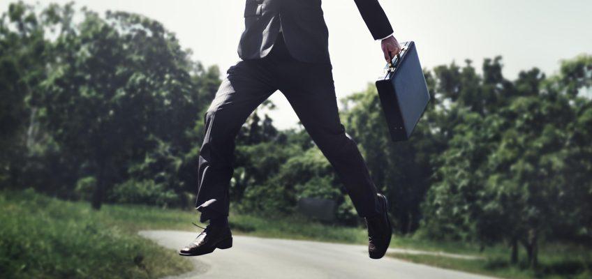 Mann macht mit Aktenkoffer in der Hand einen Luftsprung