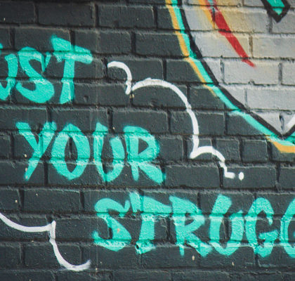 Schriftzug trust your struggle auf Backsteinwand