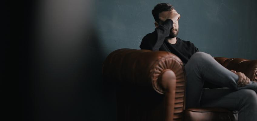 Mann sitzt auf Sofa mit Gesicht in den Händen