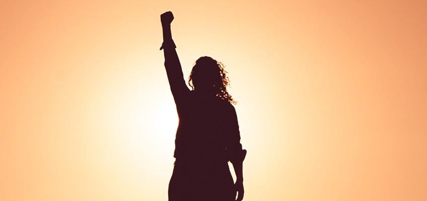 Mensch steht vor Sonne und reckt den rechten Arm gen Himmel