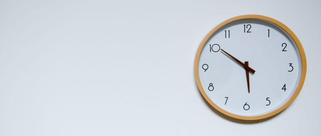 Wanduhr zeigt die Uhrzeit zehn vor sechs an