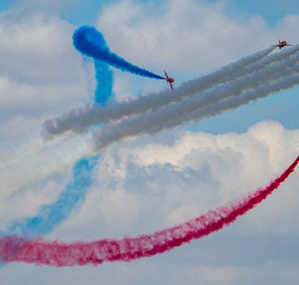 Flugzeuge zeichnen farbige Streifen am Himmel