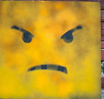 gelbes Emoji vor Backsteinwand