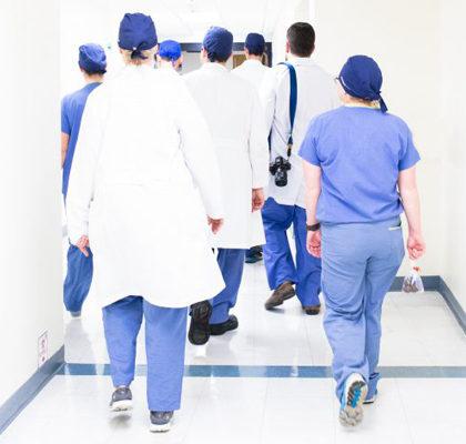 Eine Gruppe von Ärzten geht Krankenhausfllur entlang