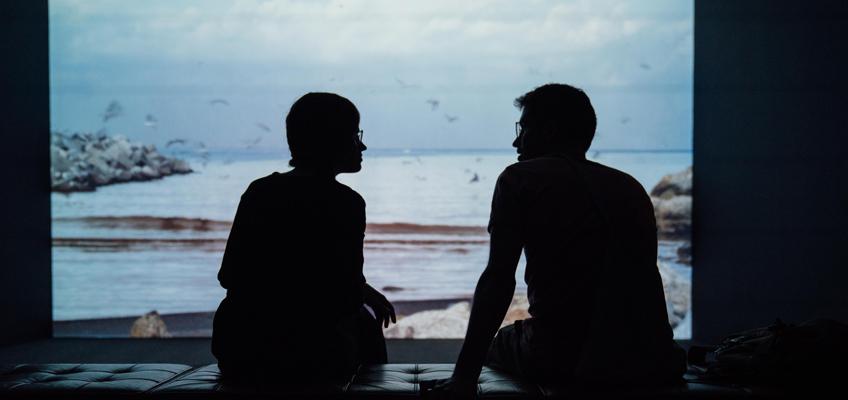 Paar sitzt auf Bank vor Panoramafenster