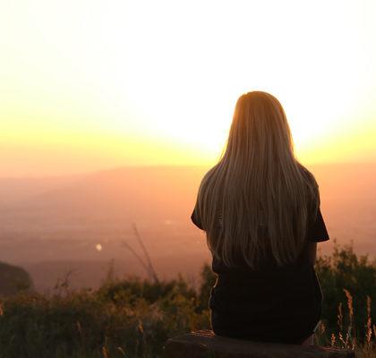 Frau sitzt auf dem Boden und schaut Sonnenaufgang zu