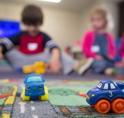 Kinder sitzen mit dem Spielzeug auf dem Fußbaoden